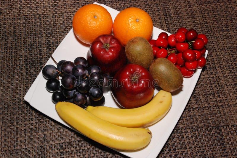 Laranjas, maçãs, uvas, quivis, cerejas, bananas na placa branca na tabela marrom imagens de stock royalty free