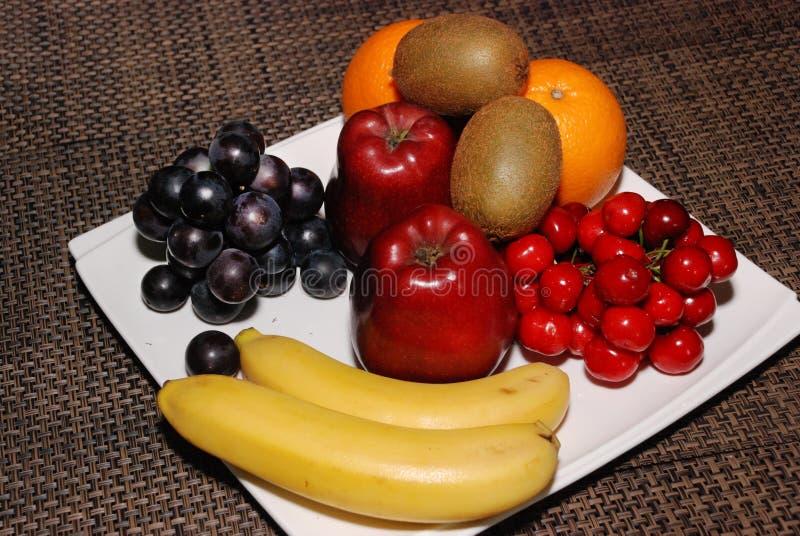 Laranjas, maçãs, uvas, quivis, cerejas, bananas na placa branca na tabela marrom imagem de stock royalty free