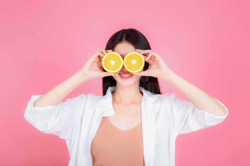 Laranjas mostrando de sorriso saudáveis da mulher asiática nova foto de stock