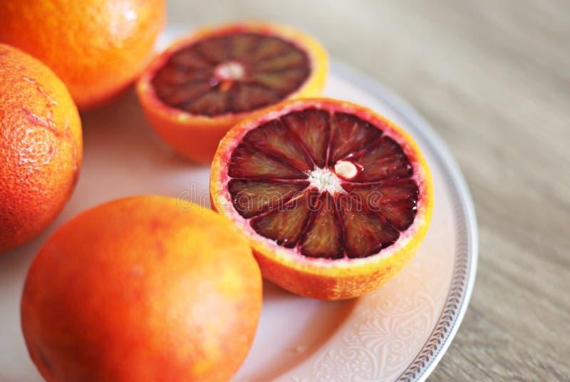 Laranjas na placa - laranja pigmentada do tarocco - laranja laranja-vermelho otimista fotografia de stock