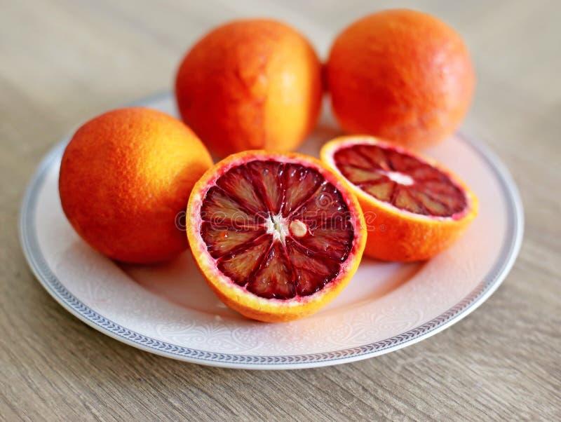 Laranjas na placa - laranja pigmentada do tarocco - laranja laranja-vermelho otimista fotografia de stock royalty free