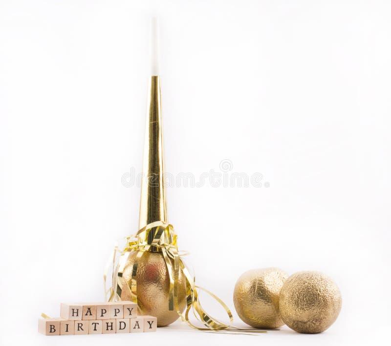 Laranjas pintadas douradas, assobio com um sinal - feliz aniversario do partido em um fundo branco - ainda vida imagem de stock