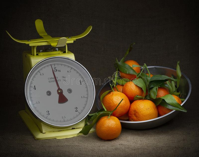 Laranjas, tangerinas em escalas na juta rústica Escuro, do claro-escuro do estilo vida ainda Tema do vintage foto de stock