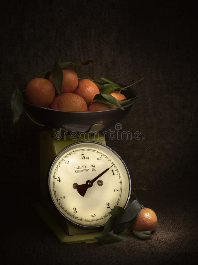 Laranjas, tangerinas em escalas na juta rústica Escuro, do claro-escuro do estilo vida ainda Tema do vintage Tiro vertical imagem de stock royalty free