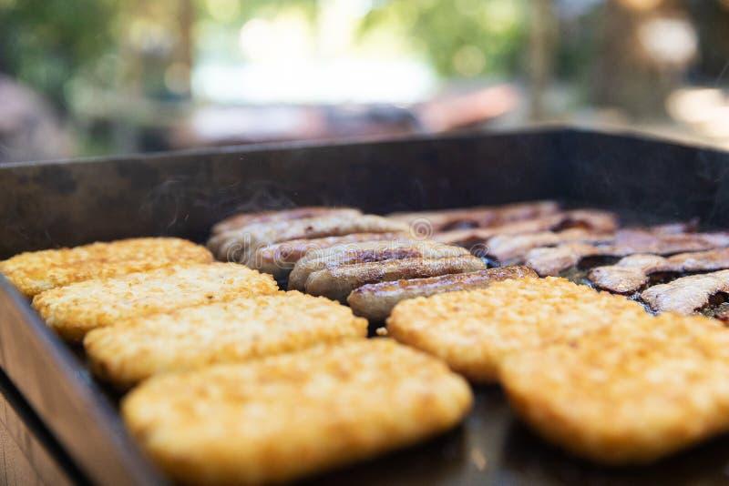 Lard, saucisse et hasbrowns sur un gril faisant cuire pour le petit déjeuner au camp photos libres de droits