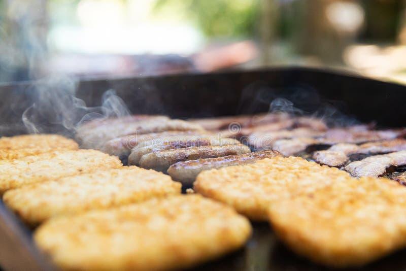 Lard, saucisse et hasbrowns sur un gril faisant cuire pour le petit déjeuner au camp photo libre de droits