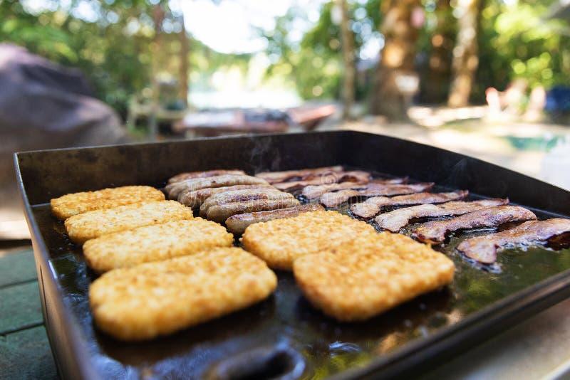 Lard, saucisse et hasbrowns sur un gril faisant cuire pour le petit déjeuner au camp photographie stock libre de droits