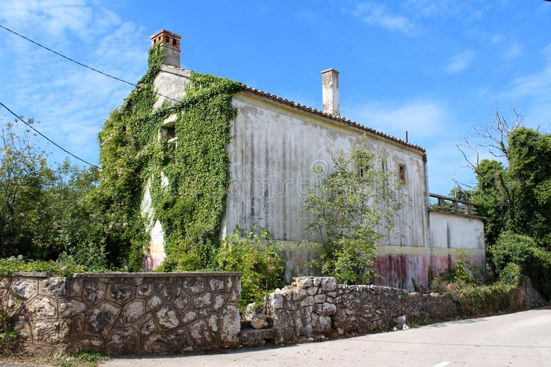 Large abandoned old stone family house partially overgrown on one side with crawler plants next to paved road surrounded with royalty free stock photos