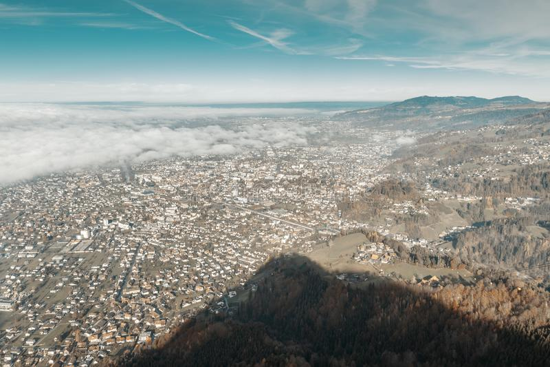 Large aerial view of city of Dornbirn in Austria in the morning fog.  royalty free stock image