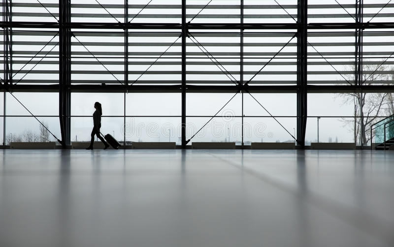 Large airport terminal. Woman walking alone in airport terminal with her roller bag royalty free stock image