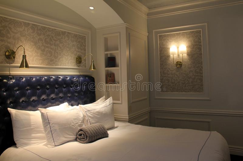 Gorgeous suite with comfortable bed and soft lighting, The Adelphi Hotel, Saratoga Springs, New York, 2018. Large airy suite inviting guests to kick off their stock photo