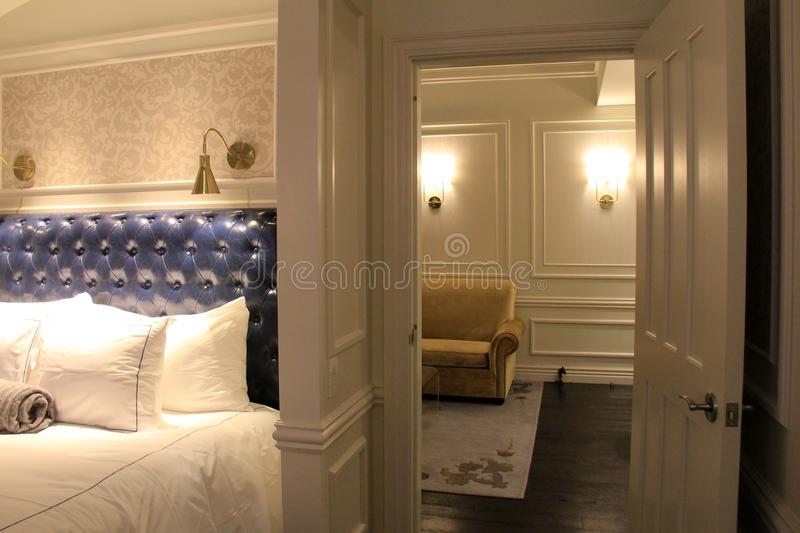 Gorgeous two room suite with comfortable bed and soft lighting, The Adelphi Hotel, Saratoga Springs, New York, 2018. Large airy suite inviting guests to kick off stock image