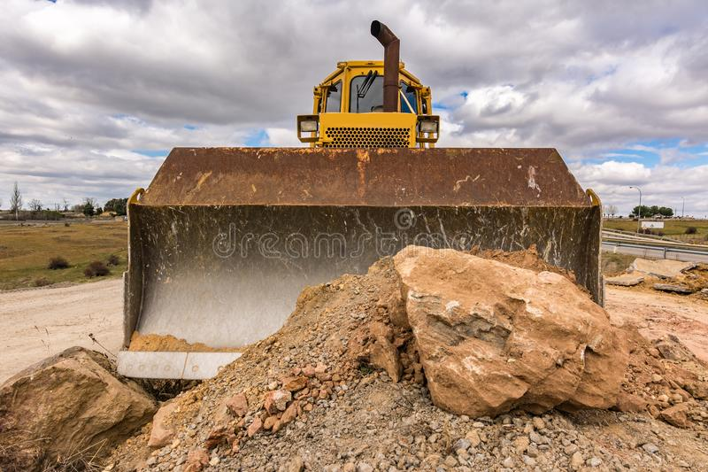 Large amount of stone and earth moved by a yellow excavator.  royalty free stock images