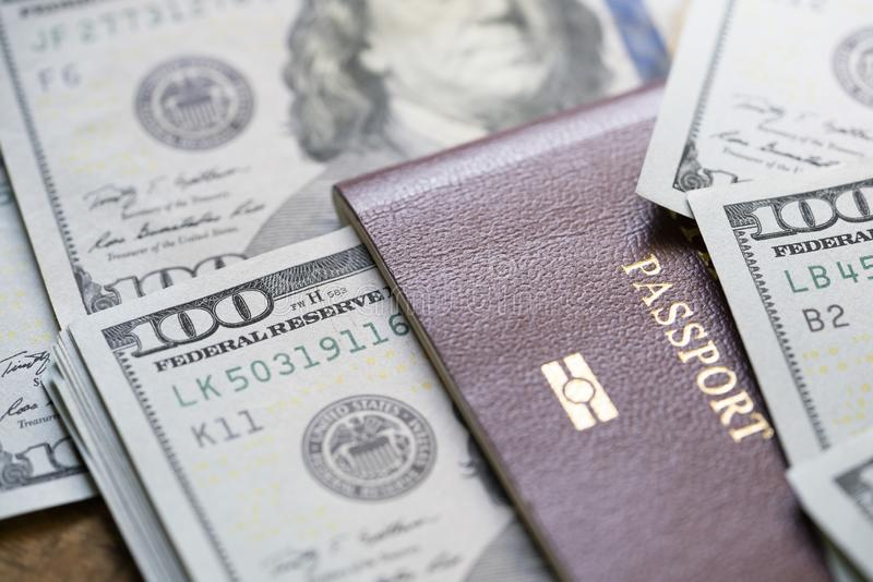 A large amount of 100 US dollar money notes on top of a stack of passports. Travel and business trip concept royalty free stock image