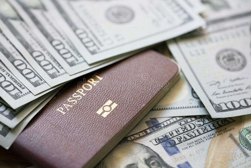 A large amount of 100 US dollar money notes on top of a stack of passports. Travel and business trip concept royalty free stock photos