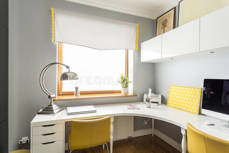 Large, angular desk in an office. Large, angular desk and hanging cabinets in an office interior in white and yellow stock photo