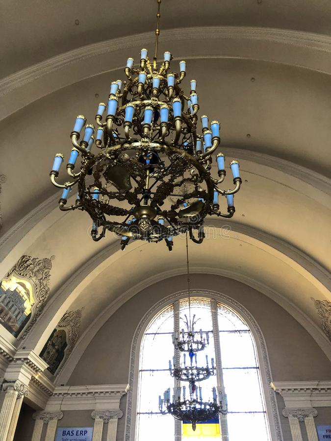 Large antique vintage expensive metal chandelier on the ceiling under the dome.  royalty free stock images
