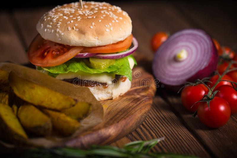 Large appetizing burger with beef, potatoes and cheese on a wooden surface. royalty free stock image
