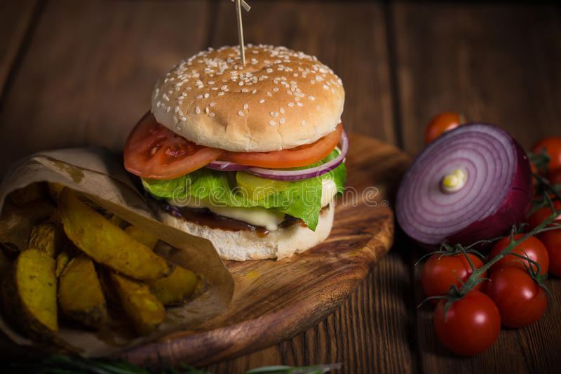 Large appetizing burger with beef, potatoes and cheese on a wooden surface. stock images
