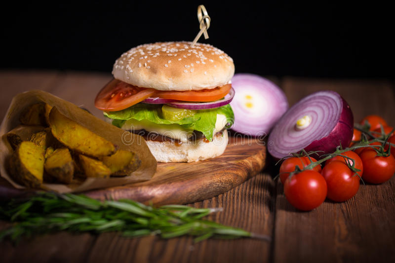 Large appetizing burger with beef, potatoes and cheese on a wooden surface. royalty free stock images