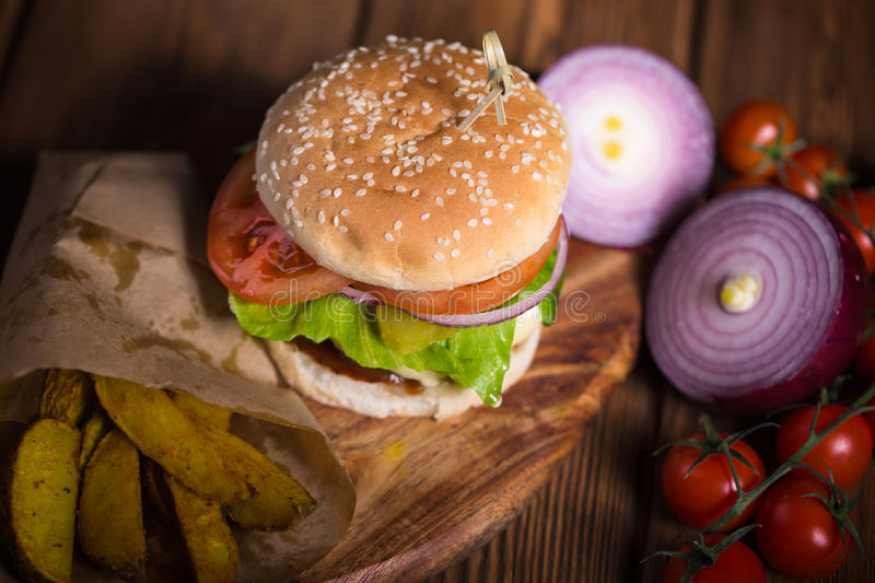Large appetizing burger with beef, potatoes and cheese on a wooden surface. stock photos