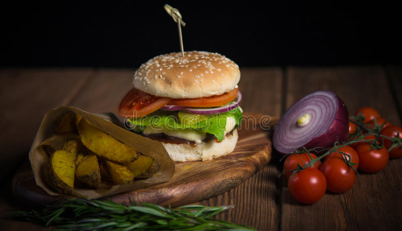 Large appetizing burger with beef, potatoes and cheese on a wooden surface. stock photography