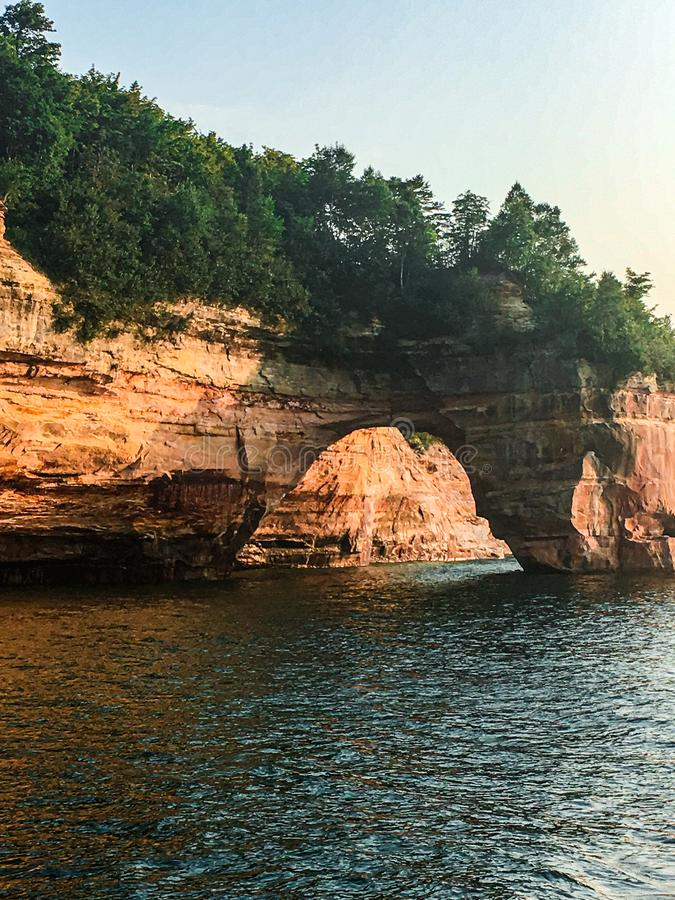 Large Archway at Pictured Rocks National Lakeshore in Michigan. A large natural arch from erosion of the Great Lake Superior. Trees growing on the tops of the stock photo