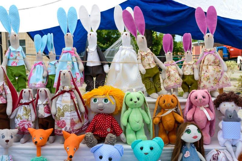 Large assortment of rag dolls. Handmade dolls, tildes. Eco toys. Fair - an exhibition of folk craftsmen stock photos