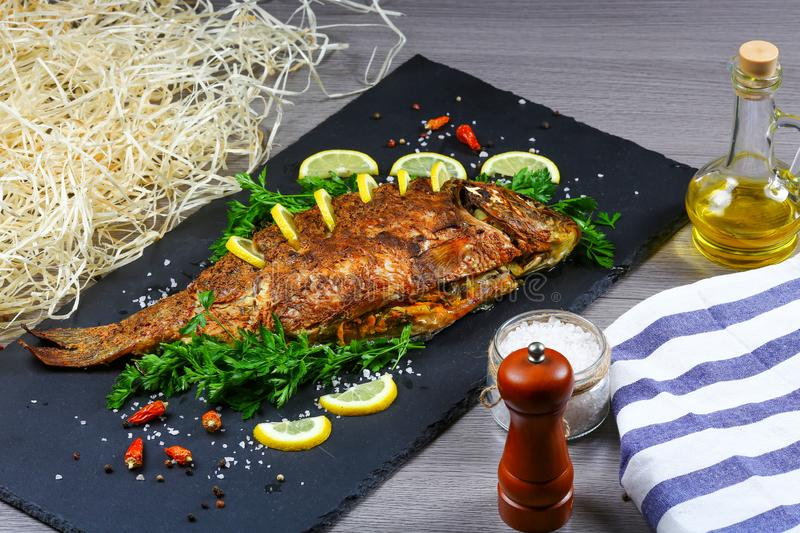 Large baked carp with herbs, lemon and spices. top view, place for text stock photo