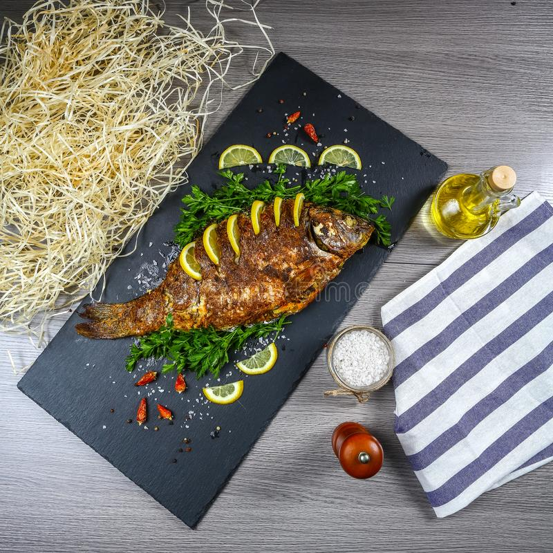 Large baked carp with herbs, lemon and spices. top view, place for text. Christmas songs dish stock image