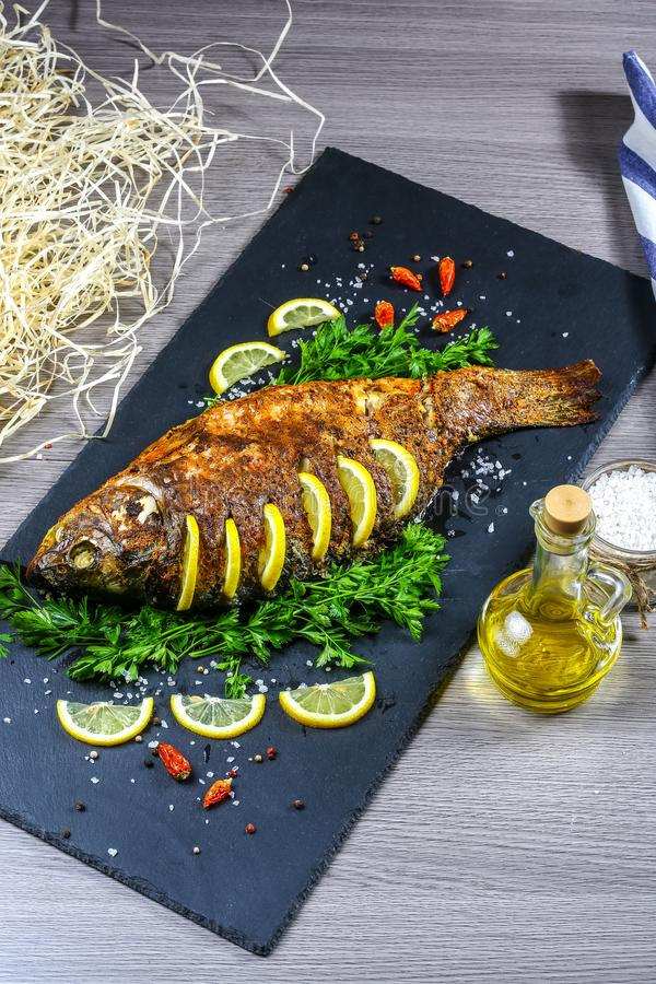 Large baked carp with herbs, lemon and spices. top view, place for text. vertical image royalty free stock image