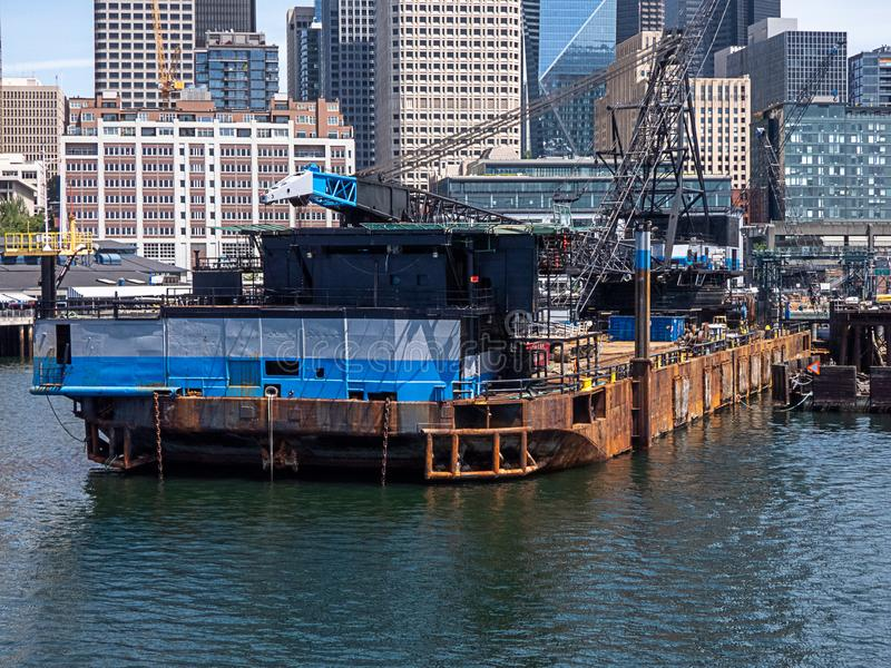 Large barge with construction equiptment and crane along the shores of city stock images