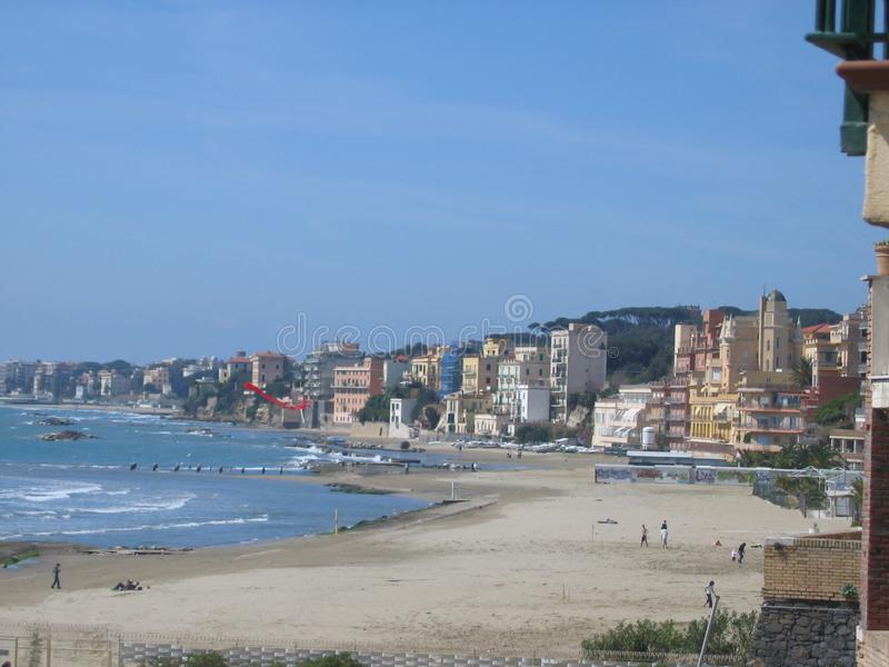 Large beach with buildings in winter in the city of Nettuno, Italy. Blue clear sky. Sunny day. Travel destination. City on the beach. Few people on the beach royalty free stock images