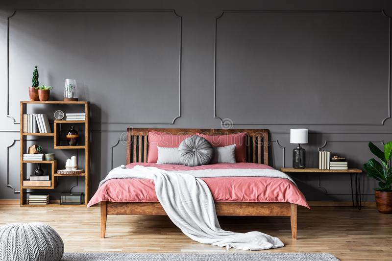 A large bed in a spacious, dark bedroom standing between a shelf. With books and ornaments and a bedside table with lamp stock photo