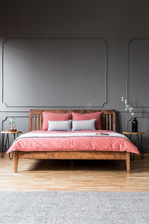 A large bed standing in a dark bedroom interior between bedside. Tables and in front of a grey rug royalty free stock photo
