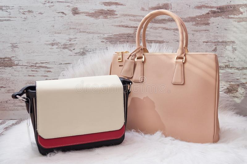 Large beige and white-red bags on a white artificial fur. Fashionable concept.  royalty free stock image
