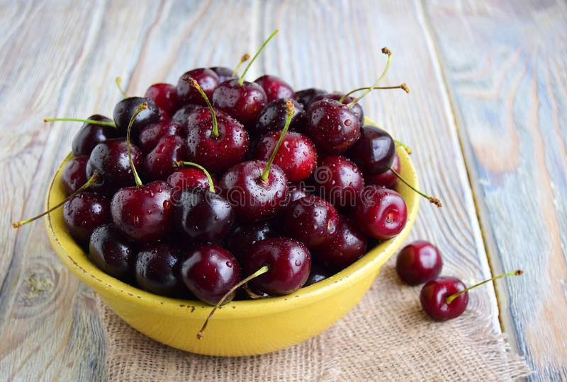 Large berries of sweet cherry are in a yellow ceramic bowl. stock image