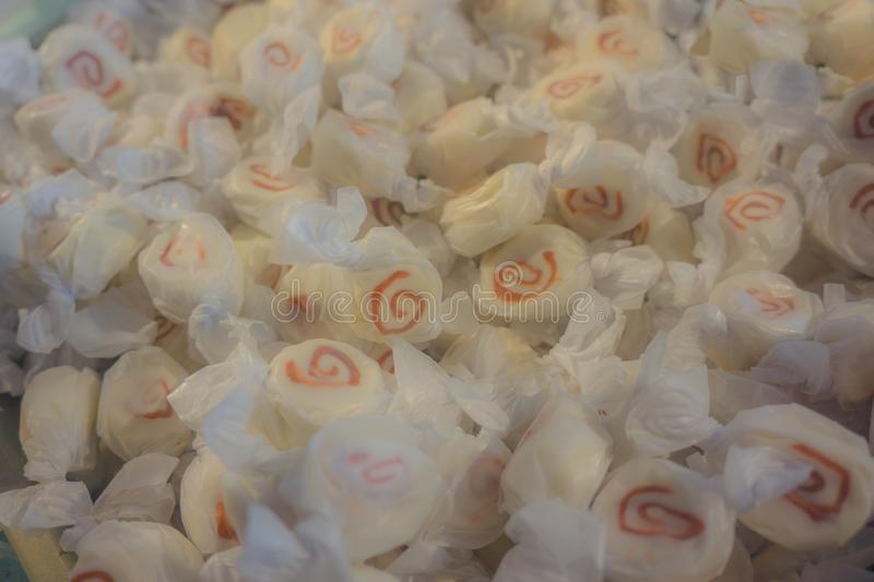 Saltwater Candy Taffy Background Soft Focus. Large bin of saltwater taffy at beachside candy store. Abstract background of hand-wrapped saltwater taffy. Copy royalty free stock photo