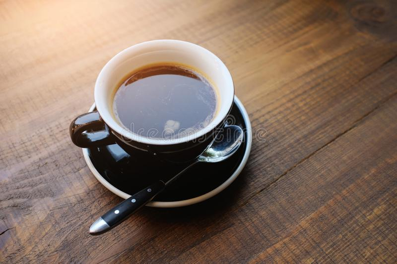 A large black Cup of coffee on a wooden table. On the plate lies the spoon. Morning. Copy space royalty free stock photography