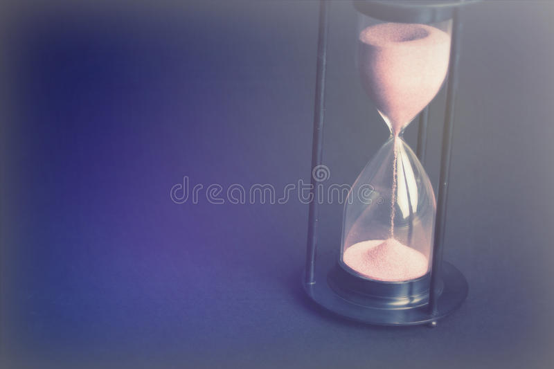 Large black hourglass against a black background. Large hourglass with pink sand against a black background stock image