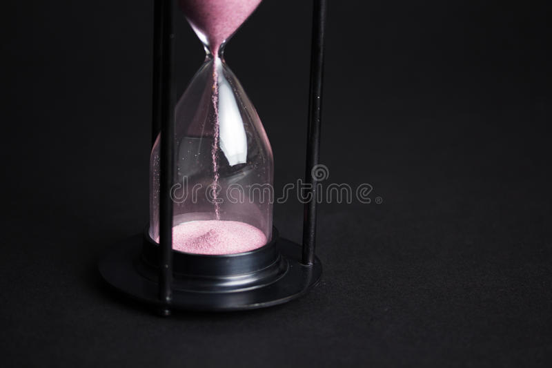 Large black hourglass against a black background. Large hourglass with pink sand against a black background royalty free stock images