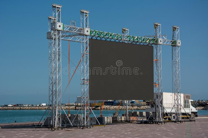 Large blank open-air outdoor LED screen for public event on sea shore. Large blank open-air outdoor LED screen for public event such as presentation, concert stock images