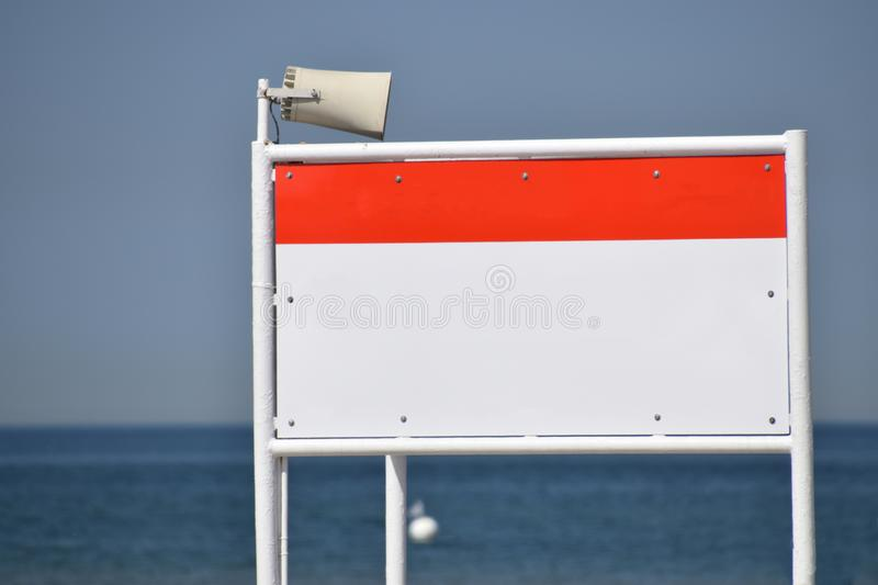 Large blank metal sign on white metal posts with blue calm ocean in background. Large blank orange and white metal sign on white metal posts with blue calm ocean stock photo