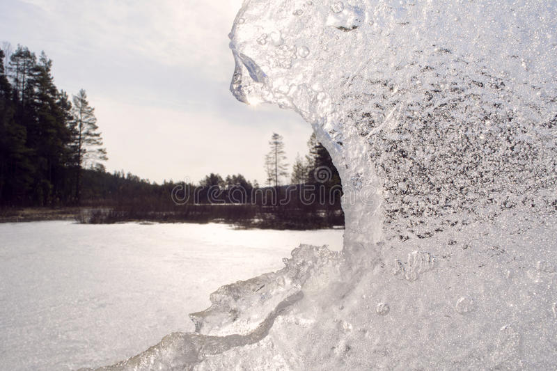 Large block of sparkling ice in front of a sunny winter landscape. Large block of sparkling ice with rough edges, almost shaped like a bear, framing a sunny royalty free stock images