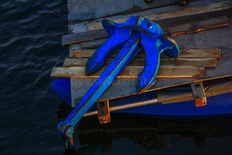 Large blue anchor lies on the edge of the catamaran royalty free stock photo