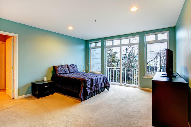 Large blue bedroom with purple bed and balcony door. Large bright blue bedroom with purple bed and balcony door royalty free stock photography