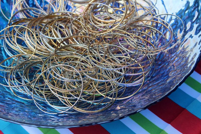 Large blue glass bowl filled with simple gold and silver bangle bracelets royalty free stock photos