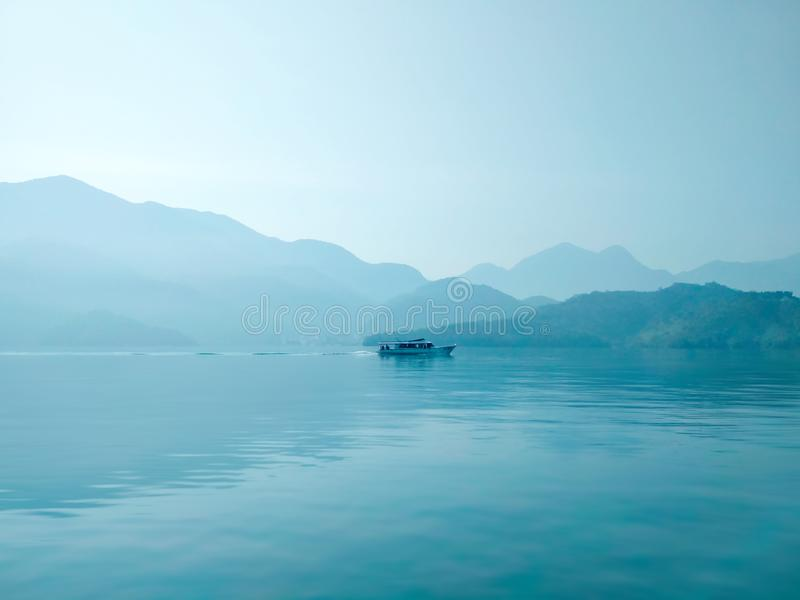 Large blue lake with lonely ship in the morning. Large blue lake surrounded by mountains with lonely ship in the morning. Light blue view with mist stock image