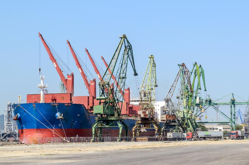 Large blue red sea cargo ship while parking in the port. Port cranes download the cargo into the ship. The work of the seaport. royalty free stock photography