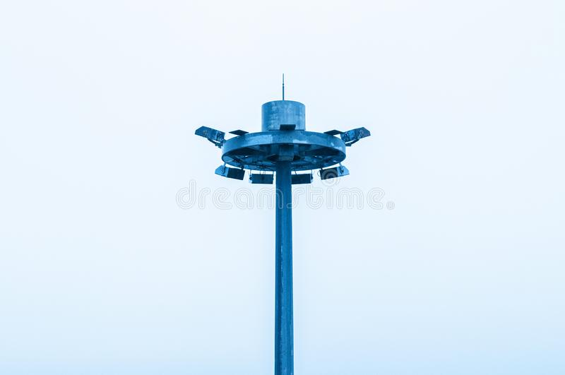 Spotlight pole with pale white sky background. Large blue spotlight pole with pale white sky background royalty free stock photos